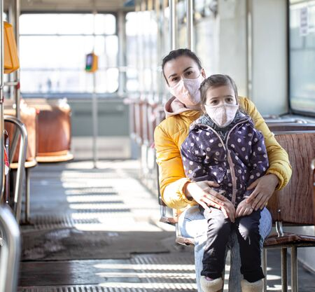 A mother with a child in an empty public transport, wearing masks during a pandemic. Coronavirus.