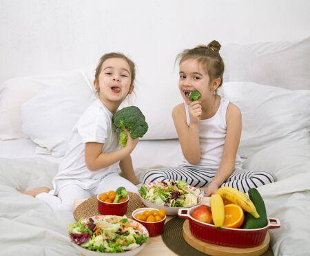 Alimentation saine à la maison. Heureux deux enfants mignons mangeant des fruits et légumes dans la chambre sur le lit. Alimentation saine pour les enfants et les adolescents.