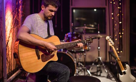 A man plays an acoustic guitar in a recording Studio. A room for musicians ' rehearsals, with a drum kit in the background. The concept of musical creativity and show business.