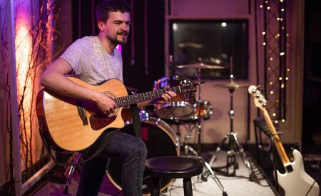 A man plays an acoustic guitar in a recording Studio. A room for musicians ' rehearsals, with a drum kit in the background. The concept of musical creativity and show business. Imagens