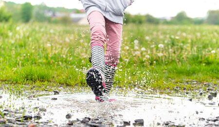 A child in rubber boots jumps in a puddle. Close up. Autumn-summer concept