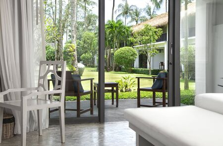 Interior of the room with a beautiful wooden chair and access to the terrace and garden. Standard-Bild