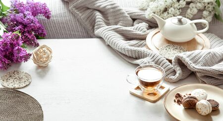 Cozy spring composition with tea and blooming lilac. Top view, flat lay