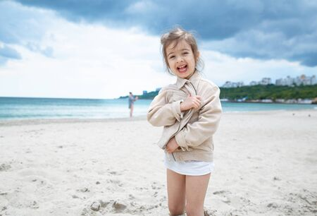 A little cute girl runs on a Sunny day on the beach by the sea. Recreation and nature. Stok Fotoğraf