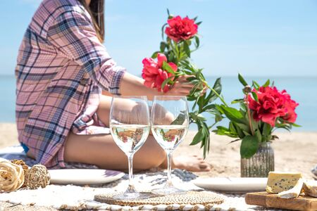 A girl is resting on the beach. A romantic picnic on the sandy shore of the beach. Against the background of flowers and glasses of drinks. The concept of summer vacation. Фото со стока