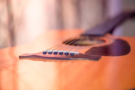 Acoustic guitar on a beautiful colored background. The concept of stringed instruments. Close up. Фото со стока