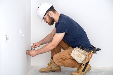 Electrician Builder at work, installation of sockets and switches. Professional in overalls with an electrician's tool. Against the background of the repair site. The concept of working as a professional. Фото со стока