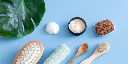 Spa composition with body care items on a colored background with a Monstera leaf . Spa concept.