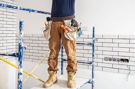 Electrician Builder at work, installation of lamps at height. Professional in overalls with an electrical tool. On the background of the repair site. The concept of working as a professional. Фото со стока