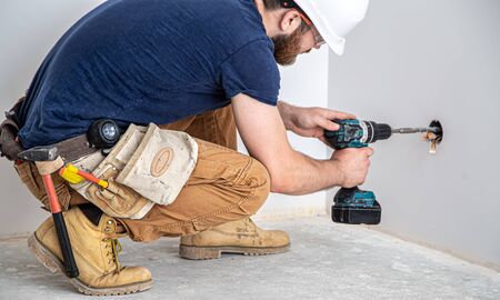 Electrician Builder at work, installation of lamps at height. Professional in overalls with a drill. On the background of the repair site. The concept of working as a professional.