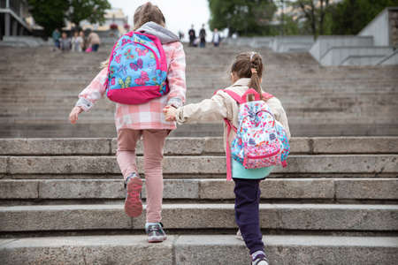 Back to school, Two girls hold hands and walk to school with a briefcase on their back.