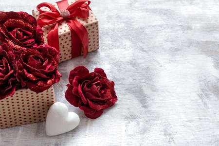 Festive background with a gift with a heart on a light background. Valentine's day and Mother's day concept.