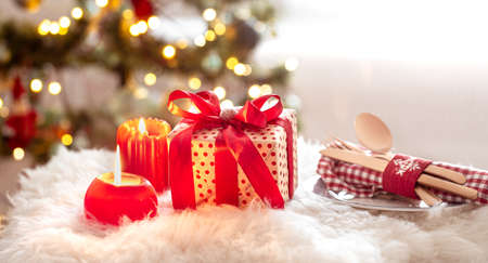 New year holiday background with a gift box in a cozy home atmosphere. The concept of the celebration. Imagens