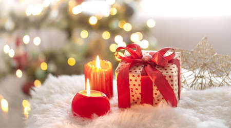 New year holiday background with a gift box in a cozy home atmosphere. The concept of the celebration.