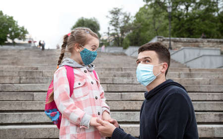 Back to school, pandemic. Father and daughter in a mask. Friendly family relationships. Education