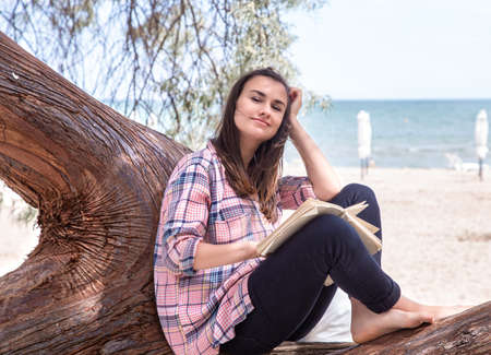 A happy girl reads a book on a tree, against the background of a sea beach. The person abstracted from everything. The concept of relaxation and tranquility. Archivio Fotografico