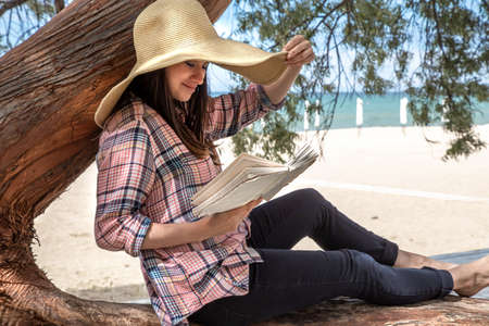 A happy girl reads a book on a tree, against the background of a sea beach. The person abstracted from everything. The concept of relaxation and tranquility. Imagens