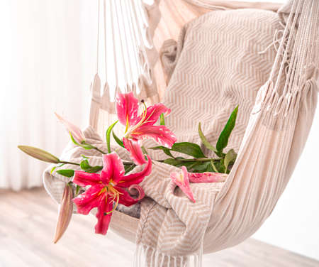 A hammock chair in boho style, with beautiful Lily flowers. Cozy interior. The concept of rest and home comfort. Space for text.