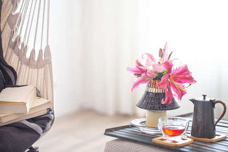A boho-style hammock chair with a stack of books. Wooden tray with teapot and Cup of tea and beautiful Lily flowers. Cozy interior. The concept of rest and home comfort. Space for text. Archivio Fotografico
