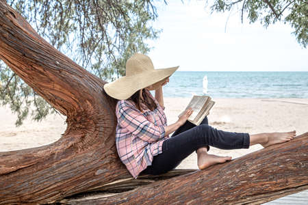 A happy girl reads a book on a tree, against the background of a sea beach. The person abstracted from everything. The concept of relaxation and tranquility.