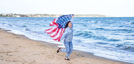 A young woman with an American flag runs by the sea. The concept of patriotism and independence day celebrations.