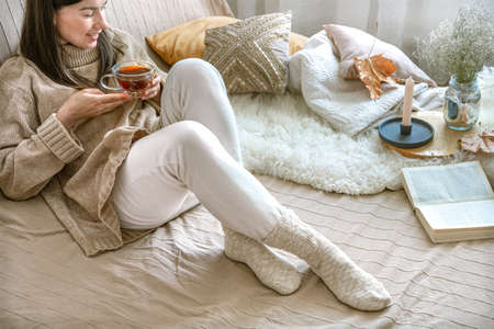 Cozy autumn or winter at home, a woman in a knitted sweater with a Cup of tea and a book.