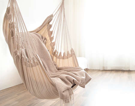 Hammock chair in boho style. Cozy interior. The concept of rest and home comfort. Space for text.
