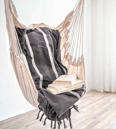A boho-style hammock chair with a stack of books. Cozy interior. The concept of rest and home comfort. Space for text.