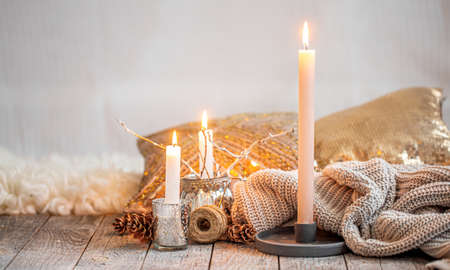 Cozy home interior, burning candles, warm sweater on a wooden table. Seasonal autumn-winter concept of a cozy home, minimal decoration, warming