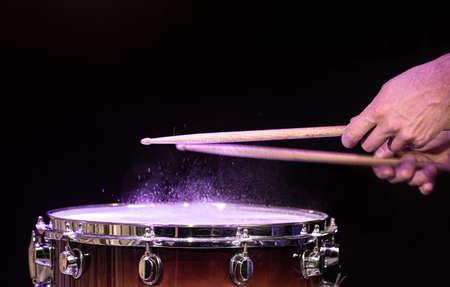 Drum sticks hitting snare drum with splashing water on black background under studio lighting copy space.