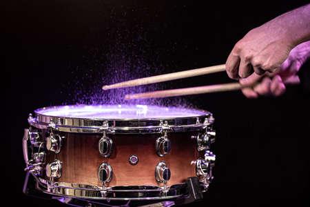 Drum sticks hitting snare drum with splashing water on black background under studio lighting close up.