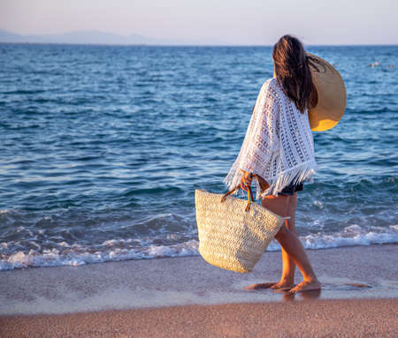 A beautiful boho model in a hat with a wicker bag walks on the beach. Archivio Fotografico