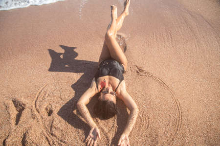 Beautiful woman in a black swimsuit lying on the sand by the sea, top view. The concept of relaxation and vacation