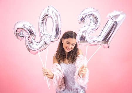 Cute young girl with a smile in a festive outfit on a pink studio background holding silver balloons from 2021 numbers