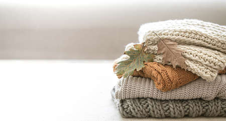 Stack of warm knitted items from autumn wardrobe close up on blurred white background copy space.