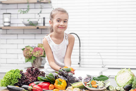 A cute little girl is holding fresh vegetables while preparing a salad copy space.
