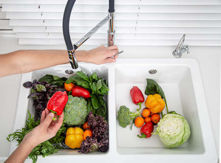 Women's hands wash vegetables in the kitchen sink of a modern kitchen. Healthy food concept. 写真素材