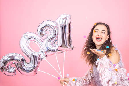 Beautiful young girl on a pink studio background rejoices with confetti and holds silver balloons from the numbers 2021 in her hand, new year party concept