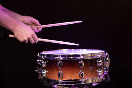Drummer playing drum sticks on a snare drum on black background close up. Stockfoto