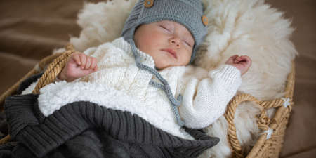The baby sleeps sweetly in a wicker cradle in a warm knitted hat under a warm blanket. Close up.