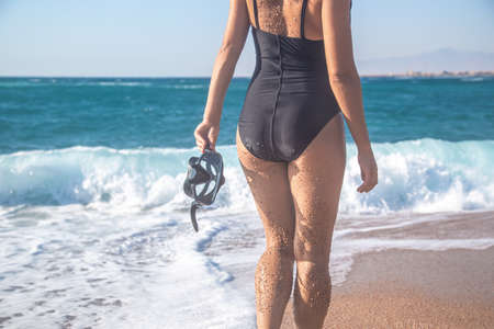 Swimming mask in the hands of a woman, close-up .Against the background of sea waves.