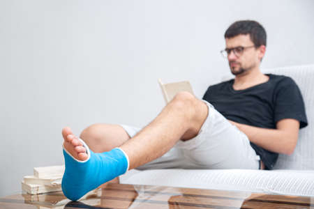 Man with broken leg in blue splint for treatment of injuries from ankle sprain reading books at the home rehabilitation.