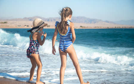 Two little girls play along the beach by the sea. The concept of friendship and recreation. 版權商用圖片