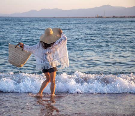 A beautiful boho model in a hat with a wicker bag walks on the beach. 版權商用圖片