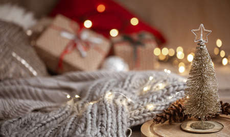 Small decorative shiny Christmas tree in the foreground on a blurred background of a knitted scarf, Christmas decorations and bokeh lights copy space.