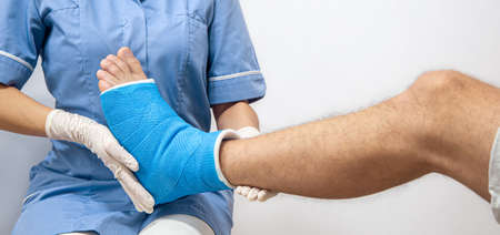 Close up of a man's leg in a cast and a blue splint after bandaging in a hospital.