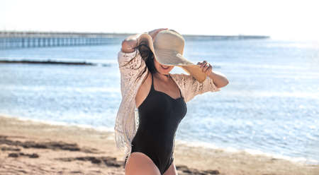 A beautiful woman in a hat and bathing suit walks on the beach near the sea.