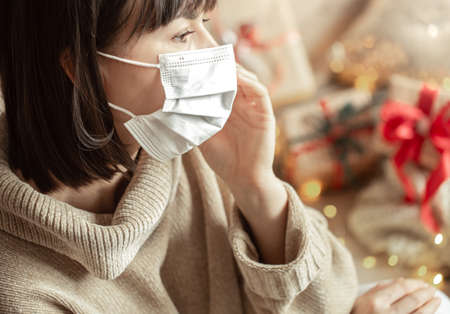 Young woman with a mask on her face in a cozy beige sweater on a blurred background with bokeh. The concept of winter holidays during the coronavirus.