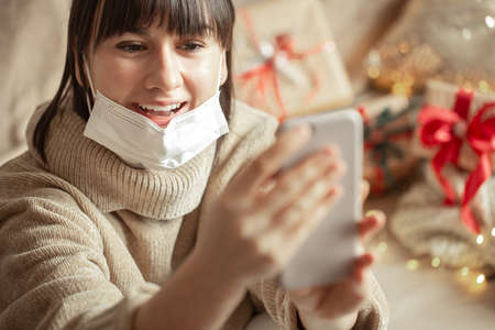 Christmas shopping online. A young girl is shopping online for the holidays during the coronavirus pandemic. 版權商用圖片