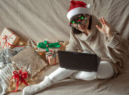 Funny girl in christmas glasses and santa claus hat sits at a laptop on a cozy background of christmas gifts.